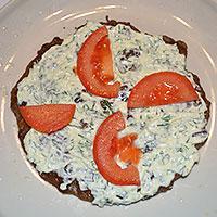 Промзываем печеночный корж и посыпаем помидорами